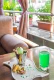 Una taza del cubo de helado del pistacho remató con los conos del maíz en la tabla blanca adentro en el mirador del verano Imagenes de archivo