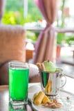 Una taza del cubo de helado del pistacho remató con los conos del maíz en la tabla blanca adentro en el mirador del verano Foto de archivo libre de regalías