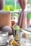 Una taza del cubo de helado del pistacho remató con los conos del maíz en la tabla blanca adentro en el mirador del verano Fotos de archivo libres de regalías