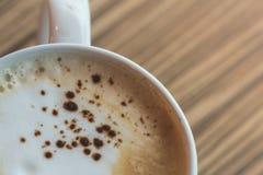 Una taza del latte caliente, arte del café en la tabla de madera en tiempo del relex Foto de archivo