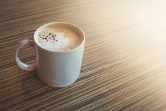 Una taza del latte caliente, arte del café en la tabla de madera en tiempo del relex Fotografía de archivo