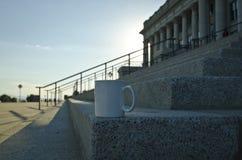 Una taza en blanco del café con leche en la esquina del capitol camina foto de archivo libre de regalías