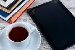 Una taza en un platillo con un café al lado de una tableta negra y de diversos libros en un fondo de madera Fotos de archivo