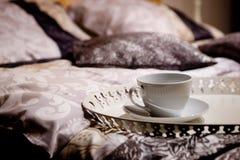 Una taza en una cama agradable Imagen de archivo