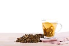 Una taza hermosa de un té verde sabroso del limón aislado en un fondo blanco Una taza en una tabla de madera ligera Copie el espa Imagenes de archivo