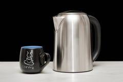 Una taza mettal de la caldera y de café Fotos de archivo libres de regalías