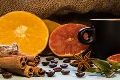 Una taza negra de café al lado del canela con los pudines y las naranjas tajadas imagen de archivo libre de regalías