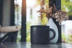 Una taza negra de café caliente con las flores secas en un florero blanco en la tabla Fotos de archivo