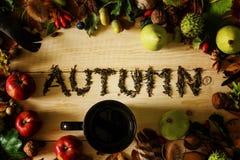 Una taza negra de té en una tabla de madera con un marco de las cosechas del otoño y de las hojas que caen imagen de archivo libre de regalías