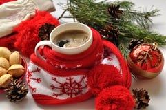 Una taza roja de café caliente, un rojo y el blanco hicieron punto la bufanda con pompones, una ramita del abeto, los conos y las Foto de archivo