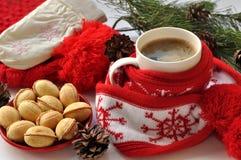 Una taza roja de café caliente, un rojo y el blanco hicieron punto la bufanda con pompones, una ramita del abeto, los conos y las Imágenes de archivo libres de regalías