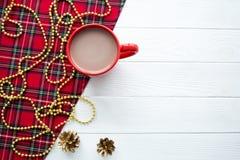 Una taza roja en la tabla blanca, fondo de la Navidad Espacio para el texto fotos de archivo libres de regalías