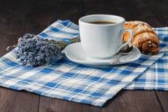 Una taza sucia después del café, del cruasán y del lavende acabados del café express Imágenes de archivo libres de regalías
