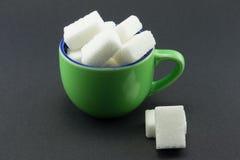 Una taza verde llena de cubos del azúcar Fotos de archivo