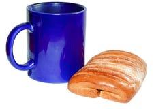 Una taza y un bollo Imagen de archivo