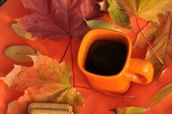 Una tazza arancio di tè, delle foglie di acero variopinte e dei biscotti su una superficie arancio Fotografia Stock Libera da Diritti