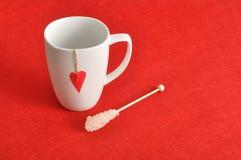 Una tazza bianca con un cuore rosso immagini stock libere da diritti