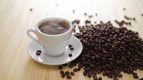Una tazza bianca di caffè d'evaporazione sulla tavola con i semi di cacao torrefatti in 4K stock footage