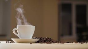 Una tazza bianca di caffè d'evaporazione sulla tavola con i semi di cacao torrefatti in 4K archivi video