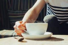 Una tazza bianca di caffè nero ed uomo come ottengala Fotografie Stock