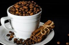 Una tazza bianca in pieno dei chicchi di caffè sta su un piattino bianco, che sta su un fondo nero immagine stock libera da diritti