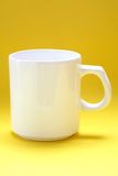 Una tazza bianca su una priorità bassa gialla Fotografie Stock Libere da Diritti