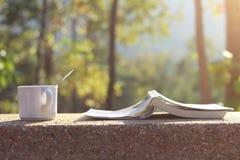 Una tazza con il libro di A nel tempo di frenaggio Immagine Stock