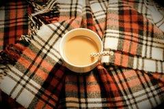 Una tazza con la paglia della carta riempita di condizione del latte e del caffè su una coperta del plaid immagine stock libera da diritti