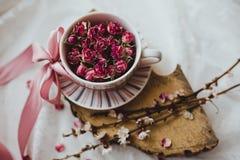 Una tazza con un piattino ha riempito di rose e di arco rosa fotografie stock libere da diritti