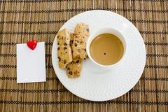 Una tazza dei biscotti di pepita di cioccolato e del caffè macchiato con il blocco note Immagine Stock