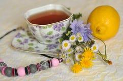 Una tazza dei fiori gialli e blu del tè, dell'estate del campo, un limone e una collana su un pizzo elegante sorge Immagine Stock