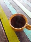 una tazza del nero su una tavola variopinta Immagine Stock