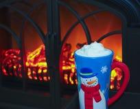 Una tazza del pupazzo di neve di cacao dal fuoco fotografia stock