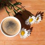 Una tazza del ramo del caffè nero dei fiori della margherita bianca su fondo di legno nel sunligh luminoso di mattina con ombra fotografie stock