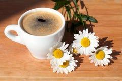 Una tazza del ramo del caffè nero dei fiori della margherita bianca su fondo di legno nel sunligh luminoso di mattina con ombra immagine stock libera da diritti