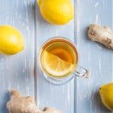 Una tazza del tè dello zenzero con il limone su un fondo di legno immagini stock libere da diritti