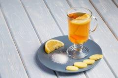 Una tazza del tè dello zenzero con il limone su un fondo di legno Immagine Stock