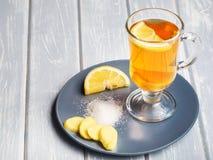 Una tazza del tè dello zenzero con il limone su un fondo di legno fotografie stock