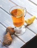 Una tazza del tè dello zenzero con il limone su un fondo di legno Fotografia Stock