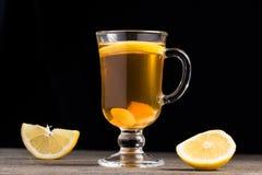 Una tazza del tè dello zenzero con il limone su un fondo di legno immagini stock