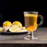Una tazza del tè dello zenzero con il limone su un fondo di legno immagine stock libera da diritti