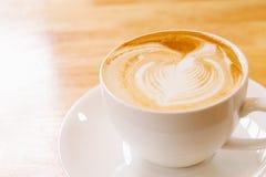 Una tazza di arte del latte sulla tavola di legno Immagini Stock Libere da Diritti