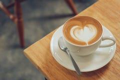 Una tazza di arte del Latte sulla tavola di legno in caffè del caffè Immagine Stock Libera da Diritti