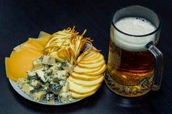Una tazza di birra e un piatto con parecchi generi di formaggio fotografie stock
