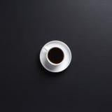 Una tazza di caffè bianca su un fondo grigio scuro dello scrittorio immagine stock