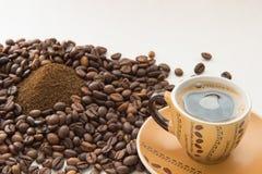 Una tazza di caffè, chicchi di caffè, caffè macinato Immagini Stock Libere da Diritti