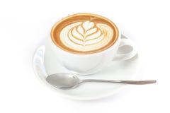 Una tazza di caffè con arte del latte sulla cima Fotografia Stock