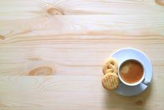 Una tazza di caffè con due biscotti di burro sulla Tabella di legno immagini stock