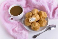 Una tazza di caffè con i profiteroles Priorità bassa bianca tazza di caffè che veste bianco di mattina dell'abito della ragazza C immagini stock