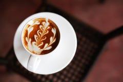 Una tazza di caffè con il modello della foglia Immagini Stock